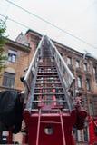 Το ξετυλιγμένο πυροσβεστικό όχημα σκαλών Οι πυροσβέστες εξαφανίζουν τη στέγη του παλαιού σπιτιού στοκ φωτογραφία με δικαίωμα ελεύθερης χρήσης