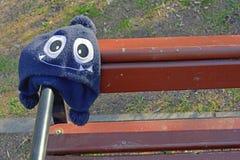 Το ξεχασμένο παιδί ΚΑΠ με το χαριτωμένο πρόσωπο τεράτων με τα μεγάλα μάτια κρεμά στον ξύλινο πάγκο Στοκ εικόνα με δικαίωμα ελεύθερης χρήσης