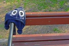 Το ξεχασμένο παιδί ΚΑΠ με το χαριτωμένο πρόσωπο τεράτων με τα μεγάλα μάτια κρεμά στον ξύλινο πάγκο Στοκ Εικόνες