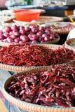 Το ξηρό κόκκινο σκόρδο κρεμμυδιών τσίλι στο καλάθι για πωλεί Στοκ Εικόνες