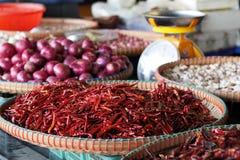 Το ξηρό κόκκινο σκόρδο κρεμμυδιών τσίλι στο καλάθι για πωλεί Στοκ Φωτογραφίες