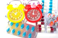 Το ξυπνητήρι στο ιατρικό πακέτο φουσκαλών παρουσιάζει χρόνο ιατρικής Στοκ Φωτογραφία