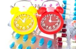Το ξυπνητήρι στο ιατρικό πακέτο φουσκαλών παρουσιάζει χρόνο ιατρικής Στοκ εικόνα με δικαίωμα ελεύθερης χρήσης
