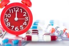 Το ξυπνητήρι στο ιατρικό πακέτο φουσκαλών παρουσιάζει χρόνο ιατρικής Στοκ φωτογραφία με δικαίωμα ελεύθερης χρήσης