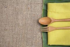 Το ξύλινα δίκρανο και το κουτάλι σχεδιάζουν στην κίτρινη πετσέτα πέρα από το φρέσκο πράσινο φύλλο μπανανών Στοκ Φωτογραφία