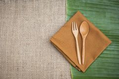 Το ξύλινα δίκρανο και το κουτάλι σχεδιάζουν στην πετσέτα brow πέρα από το φρέσκο πράσινο φύλλο μπανανών Στοκ φωτογραφίες με δικαίωμα ελεύθερης χρήσης