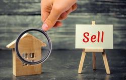 Το ξύλινα σπίτι και τα δολάρια με την επιγραφή πωλούν πώληση της ιδιοκτησίας, σπίτι προσιτή κατοικία Πώληση των διαμερισμάτων άργ στοκ φωτογραφία