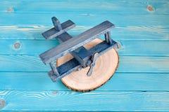 Το ξύλινο αεροπλάνο παιχνιδιών σε ένα δέντρο έκοψε σε ένα μπλε ξύλινο υπόβαθρο Στοκ Φωτογραφίες