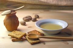 Το ξύλινο κουτάλι με το μέλι βρίσκεται στο κεραμικό πιάτο μπισκότων με το μέλι Στοκ Φωτογραφία