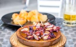 Το ξύλινο πιάτο του της Γαλικίας ύφους μαγείρεψε το χταπόδι με τις πατάτες, το ελαιόλαδο πάπρικας και gallega pulpo Λα Στοκ φωτογραφία με δικαίωμα ελεύθερης χρήσης