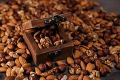 Το ξύλινο σύνολο κιβωτίων των καρυδιών και των καρυδιών διασκόρπισε γύρω, φουντούκια, ξύλα καρυδιάς και αμύγδαλα Στοκ Φωτογραφίες