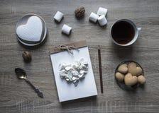 Το ξύλινο υπόβαθρο βρίσκεται ένα scrapbooking μολύβι σημειωματάριων τεχνών σε ένα marshmallows καρδιών μπισκότων εγγράφου σημειωμ Στοκ Φωτογραφία