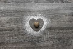 Το ξύλινο υπόβαθρο με το κονιοποιημένο χιόνι σκονών μια σκιαγραφία της καρδιάς χύνεται και βρίσκεται ένα μπισκότο υπό μορφή καρδι Στοκ εικόνες με δικαίωμα ελεύθερης χρήσης