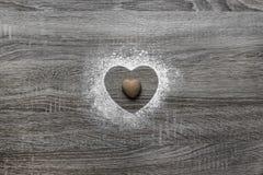 Το ξύλινο υπόβαθρο με το κονιοποιημένο χιόνι σκονών μια σκιαγραφία της καρδιάς χύνεται και βρίσκεται ένα μπισκότο υπό μορφή καρδι Στοκ φωτογραφία με δικαίωμα ελεύθερης χρήσης