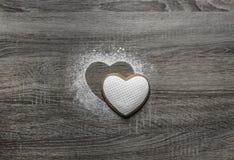 Το ξύλινο υπόβαθρο με το κονιοποιημένο χιόνι σκονών που μια σκιαγραφία της καρδιάς χύνεται κάτω από τη σκιαγραφία βρίσκεται μια μ Στοκ Εικόνες