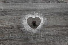 Το ξύλινο υπόβαθρο με την κονιοποιημένη σκόνη, μια σκιαγραφία της καρδιάς χύνεται με το χιόνι στο κέντρο βρίσκεται σοκολάτα γύρω  Στοκ Εικόνες