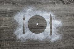 Το ξύλινο υπόβαθρο με την κονιοποιημένη σκόνη χιονισμένη με μια σκιαγραφία συσκευές πιάτων δικράνων μαχαιριών είναι μια άσπρη στρ Στοκ Φωτογραφία