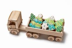 Το ξύλινο φορτηγό παιχνιδιών είναι τυχερό για το μελόψωμο Χριστουγέννων με μορφή χριστουγεννιάτικων δέντρων και snowflakes Στοκ Εικόνα