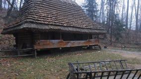 Το ξύλινο κάρρο βαγονιών εμπορευμάτων horseOld κοντά στο παλαιό παραδοσιακό ευρωπαϊκό ξύλινο του χωριού σπίτι με η στέγη απόθεμα βίντεο