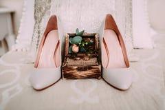 Το ξύλινο κιβώτιο με τα χρυσά γαμήλια δαχτυλίδια και τα λουλούδια στέκονται δίπλα στα κομψά νυφικά παπούτσια Στοκ εικόνες με δικαίωμα ελεύθερης χρήσης