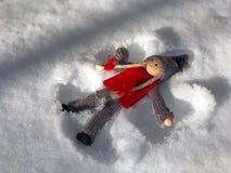 Το ξύλινο κορίτσι κουκλών βρίσκεται στο χιόνι Στοκ Εικόνες