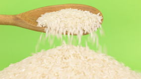 Το ξύλινο κουτάλι χύνει το ρύζι σιταριών στο σωρό του ρυζιού σε μια πράσινη οθόνη απόθεμα βίντεο