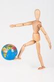 Το ξύλινο μανεκέν κλωτσά μια παγκόσμια σφαίρα στην ασέβεια που απομονώνεται στοκ εικόνες