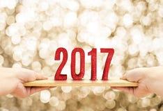 Το ξύλινο πιάτο εκμετάλλευσης χεριών με το κόκκινο καλής χρονιάς του 2017 ακτινοβολεί num Στοκ Φωτογραφίες