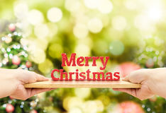 Το ξύλινο πιάτο εκμετάλλευσης χεριών με το κόκκινο Χαρούμενα Χριστούγεννας ακτινοβολεί αριθμός Στοκ Εικόνες