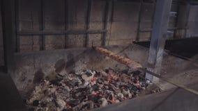 Το οβελίδιο με το νόστιμο lula kebab που βρίσκεται στο φούρνο σχαρών κοντά επάνω Το χέρι του αρχιμάγειρα ανακατώνει τον άνθρακα χ απόθεμα βίντεο