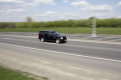 Το οικογενειακό αυτοκίνητο πηγαίνει γρήγορα στο δρόμο στοκ εικόνα