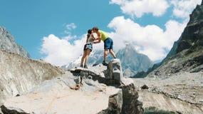 Το οικογενειακό ζεύγος των τουριστών στο οδοιπορικό βουνών αναρριχείται στην κορυφή της πέτρας και αυξάνει τα χέρια τους επάνω, φ στοκ εικόνα με δικαίωμα ελεύθερης χρήσης