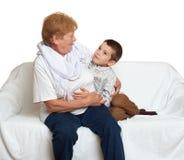 Το οικογενειακό πορτρέτο στο άσπρο υπόβαθρο, ευτυχείς άνθρωποι κάθεται στον καναπέ ηλικιωμένες γυναίκες εγγονών γιαγιάδων εγγονιώ Στοκ Εικόνα