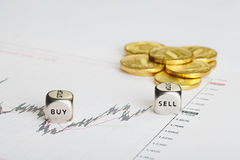 Το οικονομικό διάγραμμα, νομίσματα και χωρίζει σε τετράγωνα τους κύβους με τις λέξεις ΠΩΛΕΙ ΑΓΟΡΑΖΕΙ. Στοκ Εικόνες