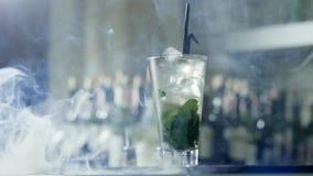 Το οινοπνευματώδες κοκτέιλ με τους κύβους πάγου και το πράσινο φύλλωμα στο μεγάλο γυαλί με τα μαύρα πλαστικά άχυρα στέκεται στον  φιλμ μικρού μήκους