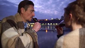 Το οινόπνευμα ποτών ανδρών και γυναικών από τα γυαλιά κρασιού κλείνει επάνω Γυαλιά κρασιού γυαλιών κουδουνίσματος ζεύγους στο υπό απόθεμα βίντεο