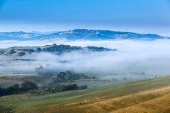 Το ομιχλώδες τοπίο παραμυθιού των Tuscan τομέων στην ανατολή Στοκ Εικόνες