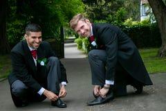Το ομοφυλοφιλικό ζεύγος των νεόνυμφων θέτει για τις φωτογραφίες whiel τις δένοντας δαντέλλες παπουτσιών στοκ εικόνες
