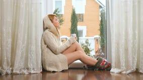 Το ονειρεμένος κορίτσι στο πουλόβερ πίνει την καυτή συνεδρίαση τσαγιού στο πάτωμα κοντά στο παράθυρο απόθεμα βίντεο