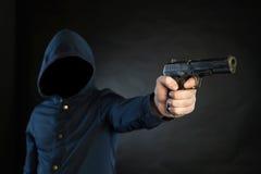Το οπλισμένο πρόσωπο σε ένα hoodie δείχνει ένα περίστροφο στο στόχο Στοκ εικόνα με δικαίωμα ελεύθερης χρήσης