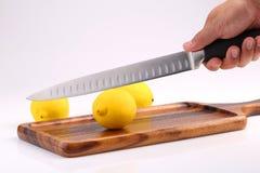 Το οργανικό φρέσκο λεμόνι στον ξύλινο δίσκο με το μαχαίρι κουζινών είναι υπό εξέταση Στοκ Φωτογραφίες