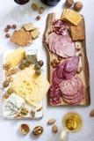 Το ορεκτικό των διάφορων τύπων λουκάνικων, κρεάτων, τυριών και κροτίδων σε έναν ξύλινο πίνακα, εξυπηρέτησε στο κρασί στοκ εικόνα με δικαίωμα ελεύθερης χρήσης