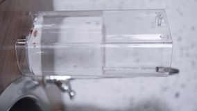 Το ορθογώνιο πλαστικό εμπορευματοκιβώτιο της μηχανής καφέ γεμίζουν με το νερό στην κουζίνα απόθεμα βίντεο