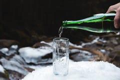 Το ορυκτό μεταλλικό νερό χύνεται από ένα πράσινο μπουκάλι γυαλιού σε μια σαφή κούπα γυαλιού Στοκ Φωτογραφία