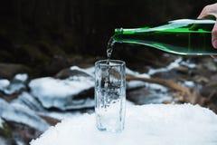 Το ορυκτό μεταλλικό νερό χύνεται από ένα πράσινο μπουκάλι γυαλιού σε μια σαφή κούπα γυαλιού Στοκ Εικόνα