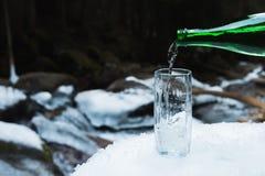 Το ορυκτό μεταλλικό νερό χύνεται από ένα πράσινο μπουκάλι γυαλιού σε μια σαφή κούπα γυαλιού Στοκ εικόνα με δικαίωμα ελεύθερης χρήσης