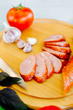 Το λουκάνικο, ο τέμνοντες πίνακας και το μαχαίρι τακτοποίησαν σε έναν ξύλινο πίνακα για ένα πρόχειρο φαγητό στην επαρχία Στοκ Εικόνες