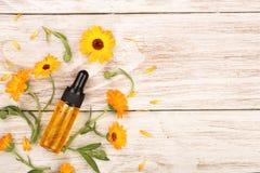 Το ουσιαστικό πετρέλαιο Aromatherapy με marigold ανθίζει στο άσπρο υπόβαθρο με το διάστημα αντιγράφων για το κείμενό σας Τοπ όψη Στοκ Εικόνες