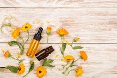 Το ουσιαστικό πετρέλαιο Aromatherapy με marigold ανθίζει στο άσπρο υπόβαθρο με το διάστημα αντιγράφων για το κείμενό σας Τοπ όψη Στοκ Φωτογραφία