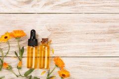 Το ουσιαστικό πετρέλαιο Aromatherapy με marigold ανθίζει στο άσπρο υπόβαθρο με το διάστημα αντιγράφων για το κείμενό σας Τοπ όψη Στοκ Φωτογραφίες